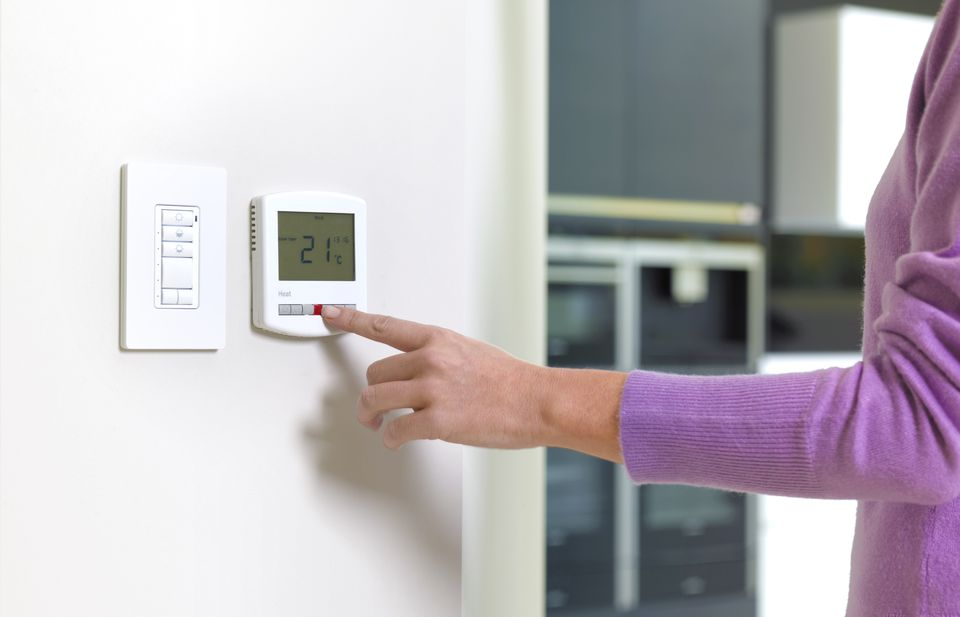 Woman adjusts a thermostat