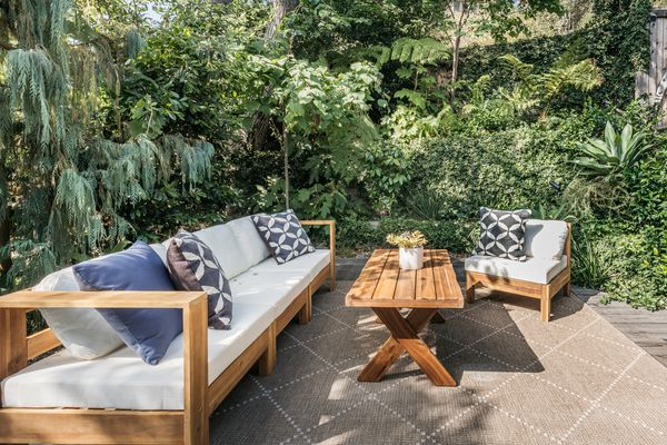 Wood patio furniture with white cushions and patterned throw pillows surrounded by trees