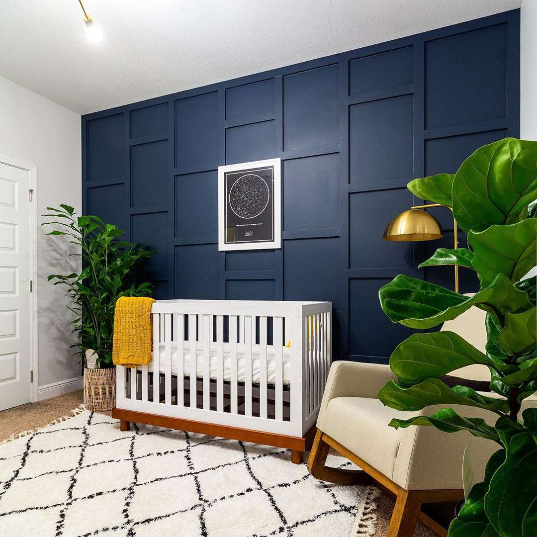 Modern boho nursery with wood-paneled navy blue accent wall.