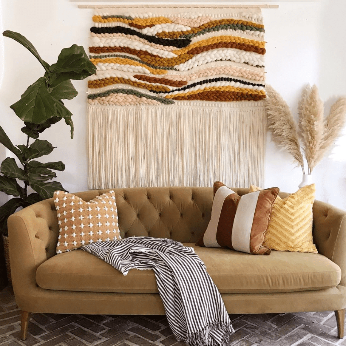 A large weaving hanging over a couch.