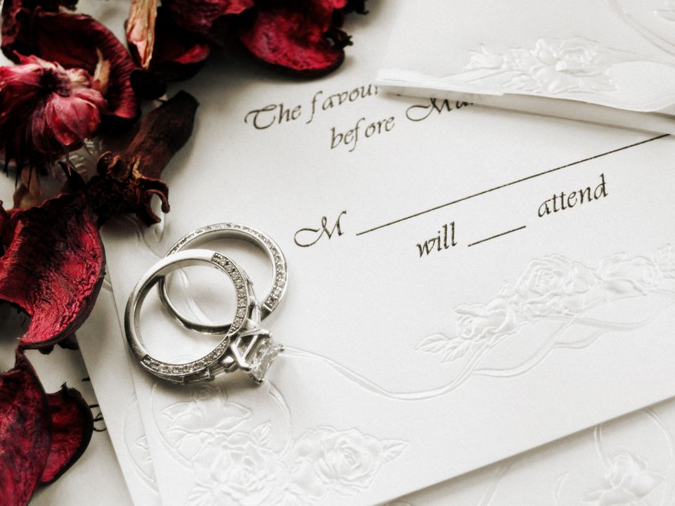 Wedding invitation RSVP with wedding rings and dried rose petals