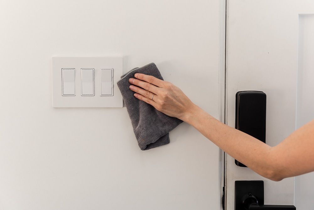 Gray microfiber cloth wiping down walls with flat paint