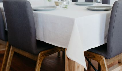 A table with a white tablecloth and gray chairs