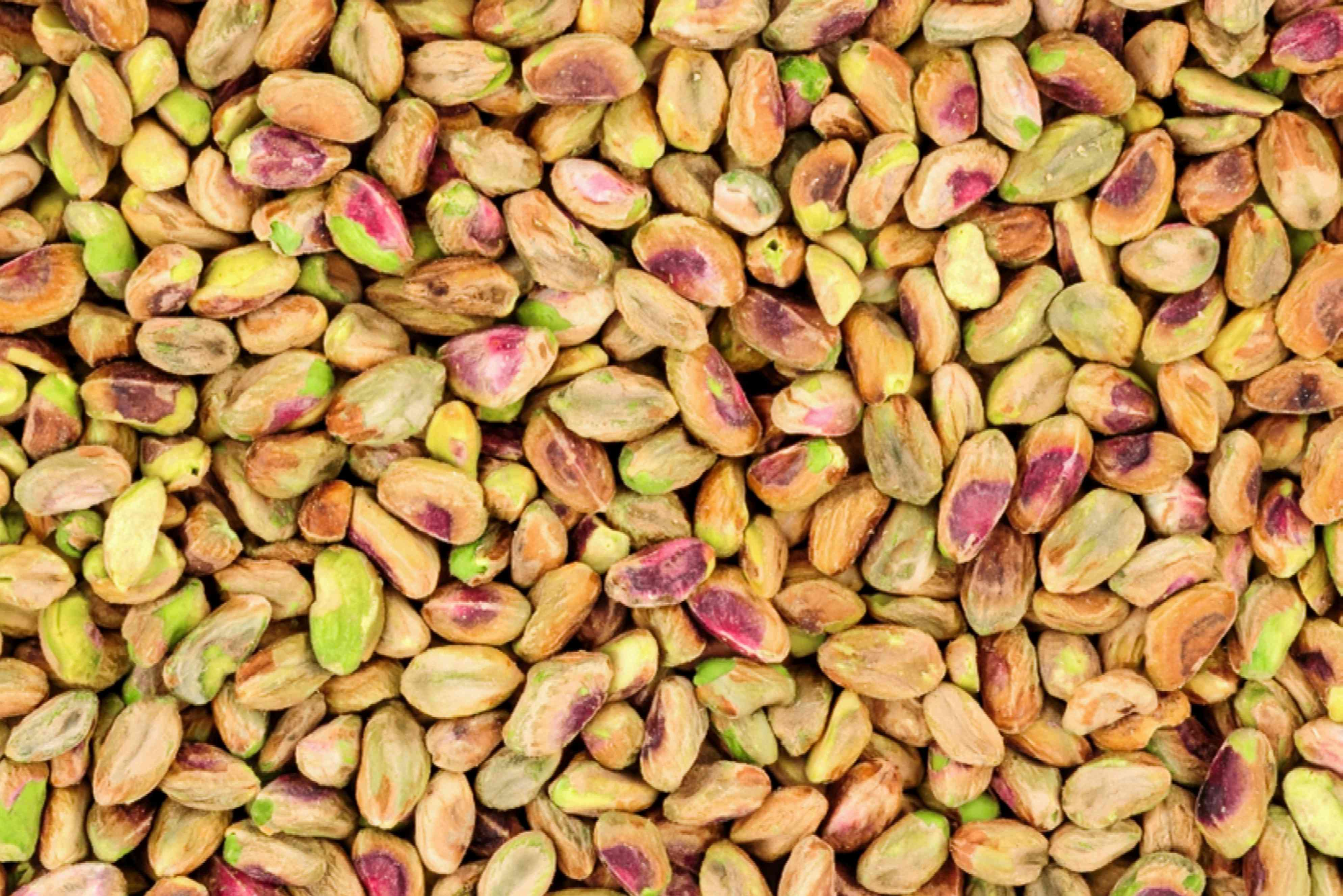 Harvested pistachio nuts with red and green spots stacked on each other closeup