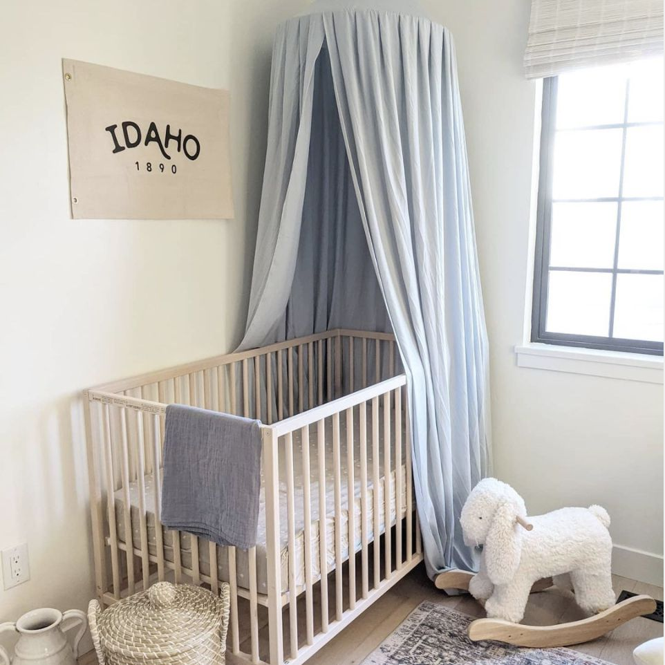nursery with powder blue canopy and off white decor
