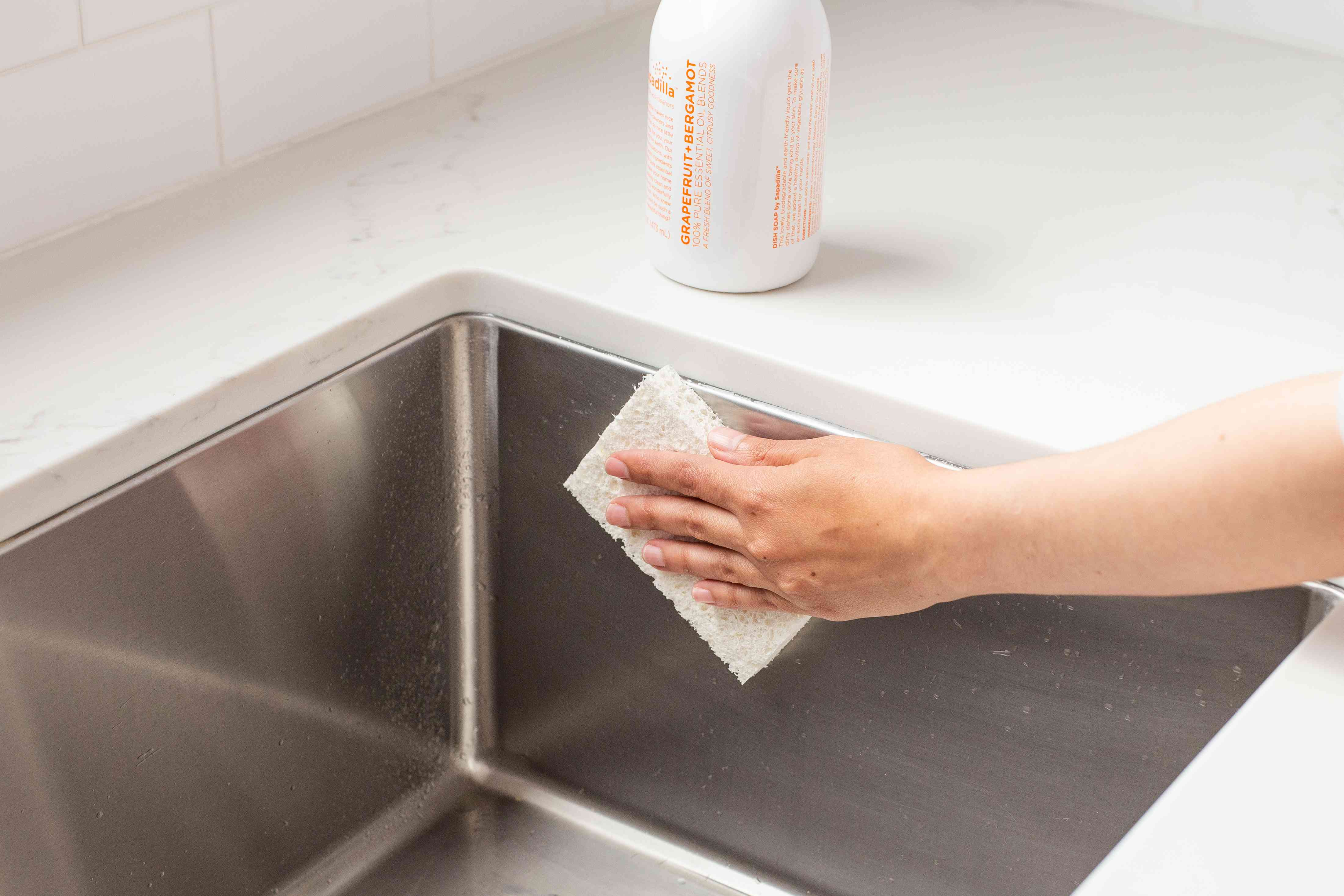 Dishwashing liquid and white sponge quickly cleaning stainless steel sink