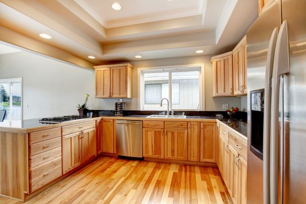 Wood kitchen with black counter tops, hardwood floor, white coffered ceiling