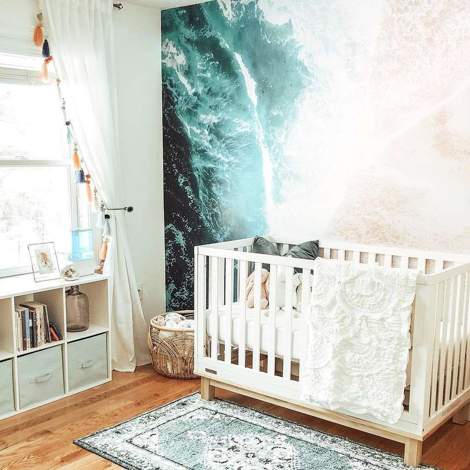 Boho-inspired beach-themed nursery with graphic ocean mural