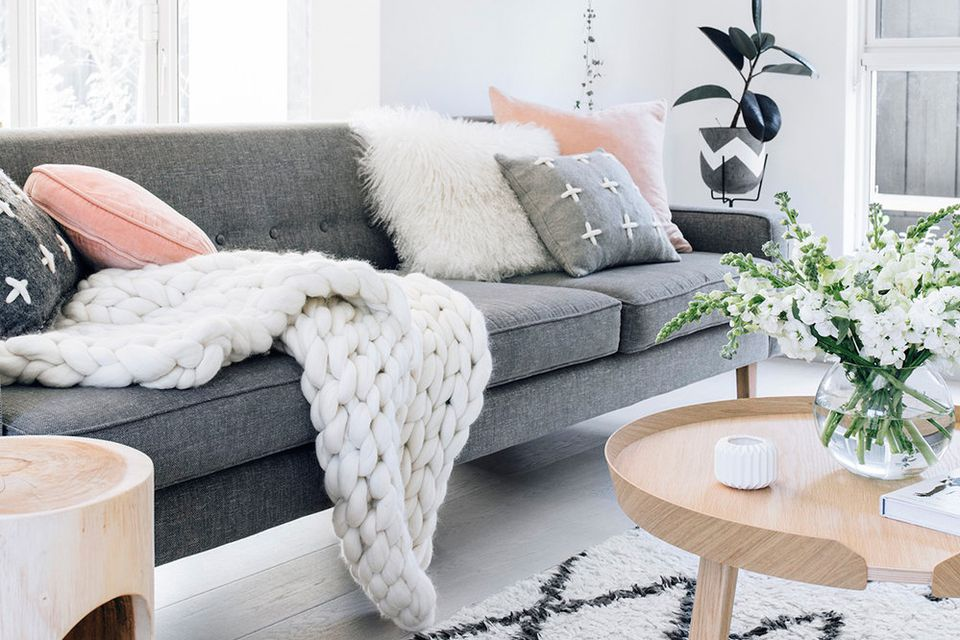 scandi style couch with pillows and a fuzzy blanket