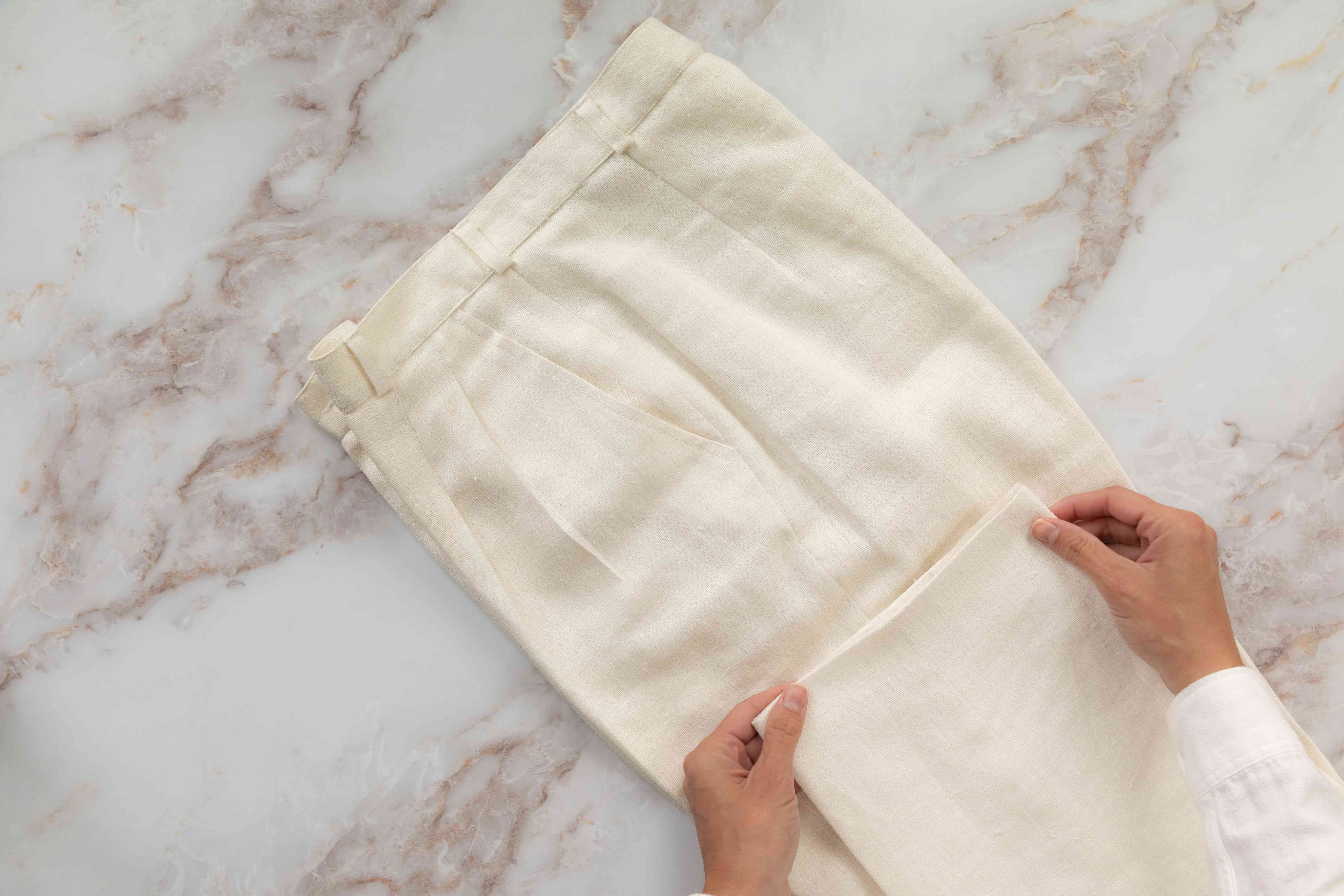 Cream-colored pants with creases folded in half with pant cuff folded up toward leg pant