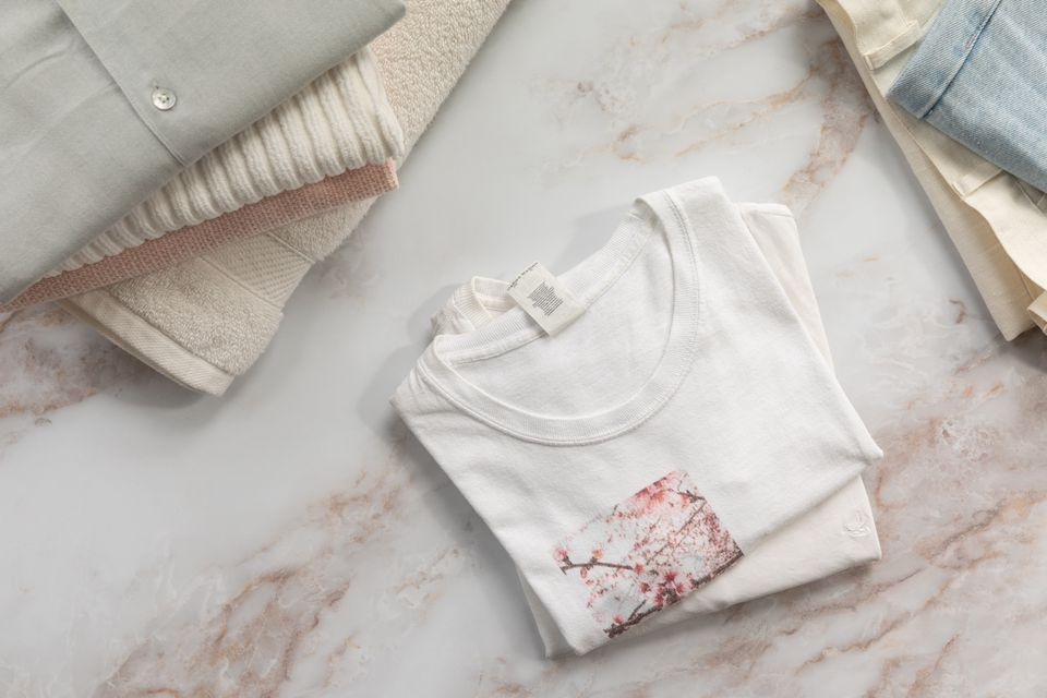 Folded white shirts in middle of white marbled surface next to other folded clothes