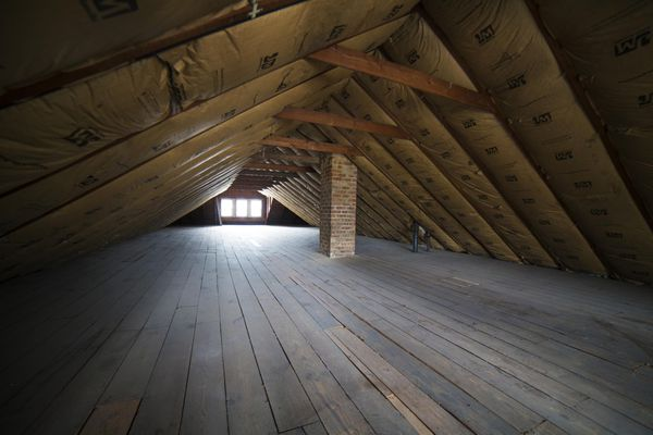 An empty attic with insulation on a roof