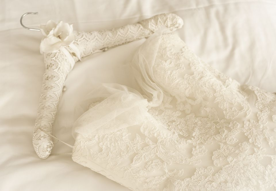 A lace wedding dress on a bed