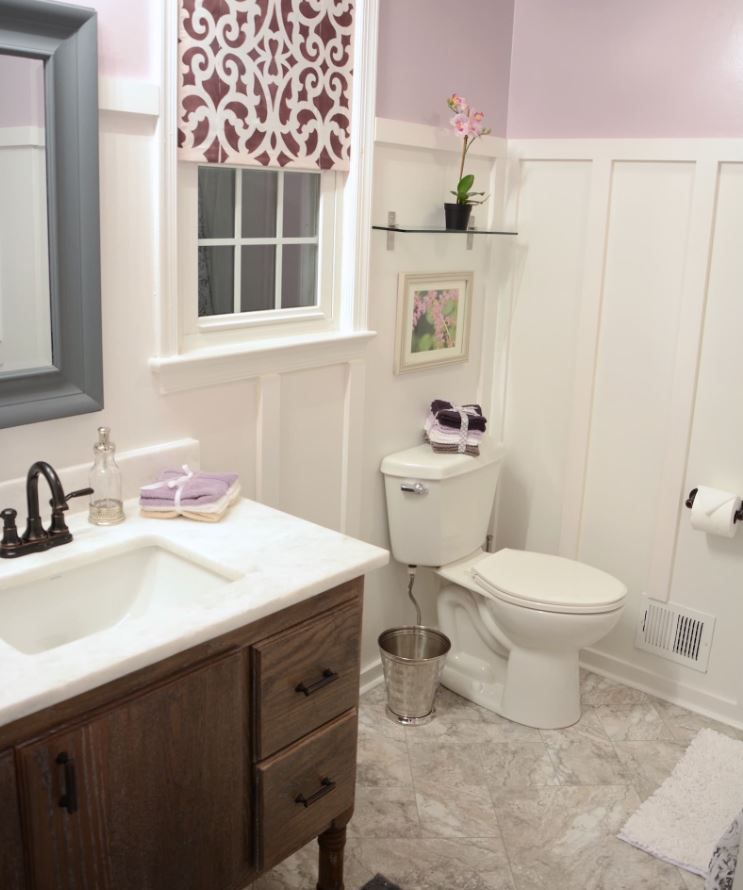 Updated bathroom with wain scoting, marble floor, and pink and lavender details.