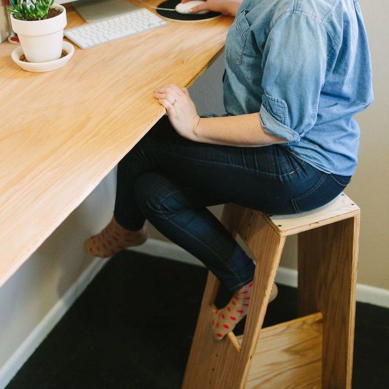 Una mujer sentada en un taburete moderno de bar de madera frente a una computadora
