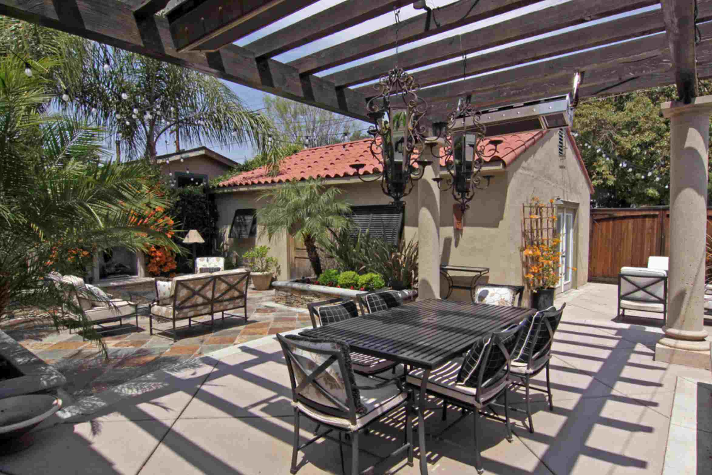 covered patio outdoor dining room stucco house terra cotta roof