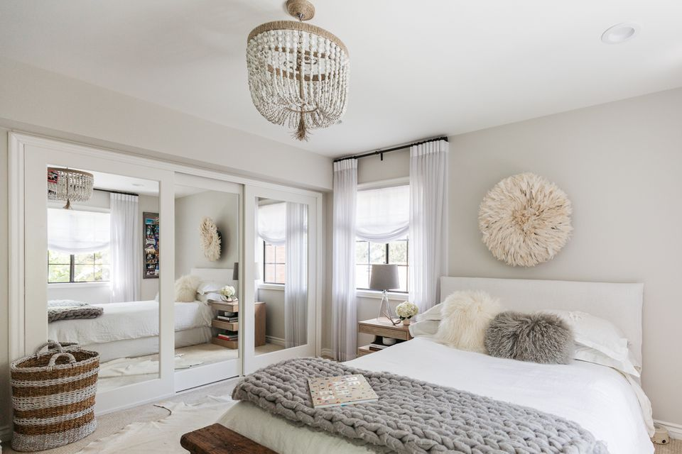 Primary bedroom with nontraditional chandelier light hanging in center of ceiling