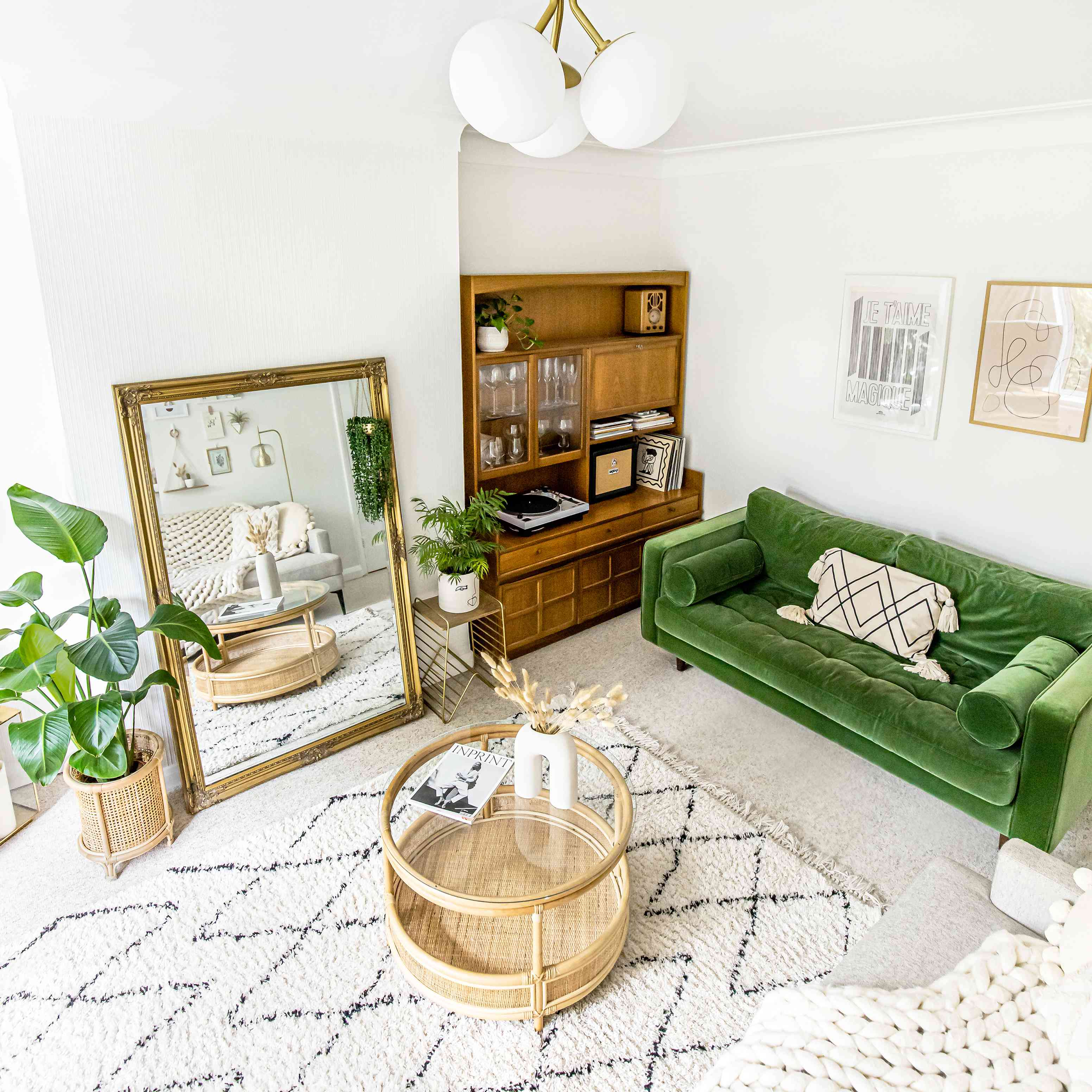 modern light fixture on ceiling of living room with green sofa