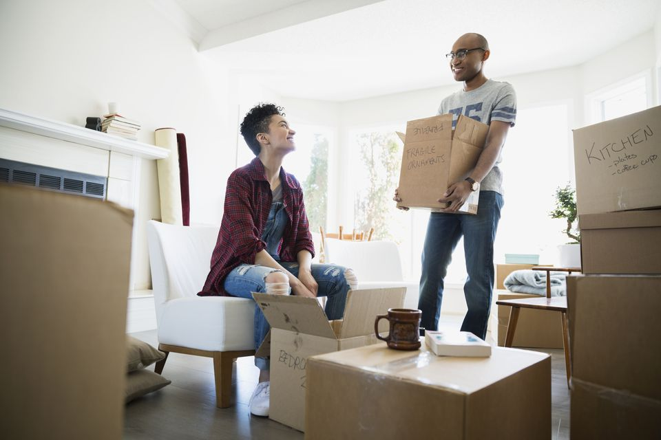 Couple unpacking belongings from moving boxes