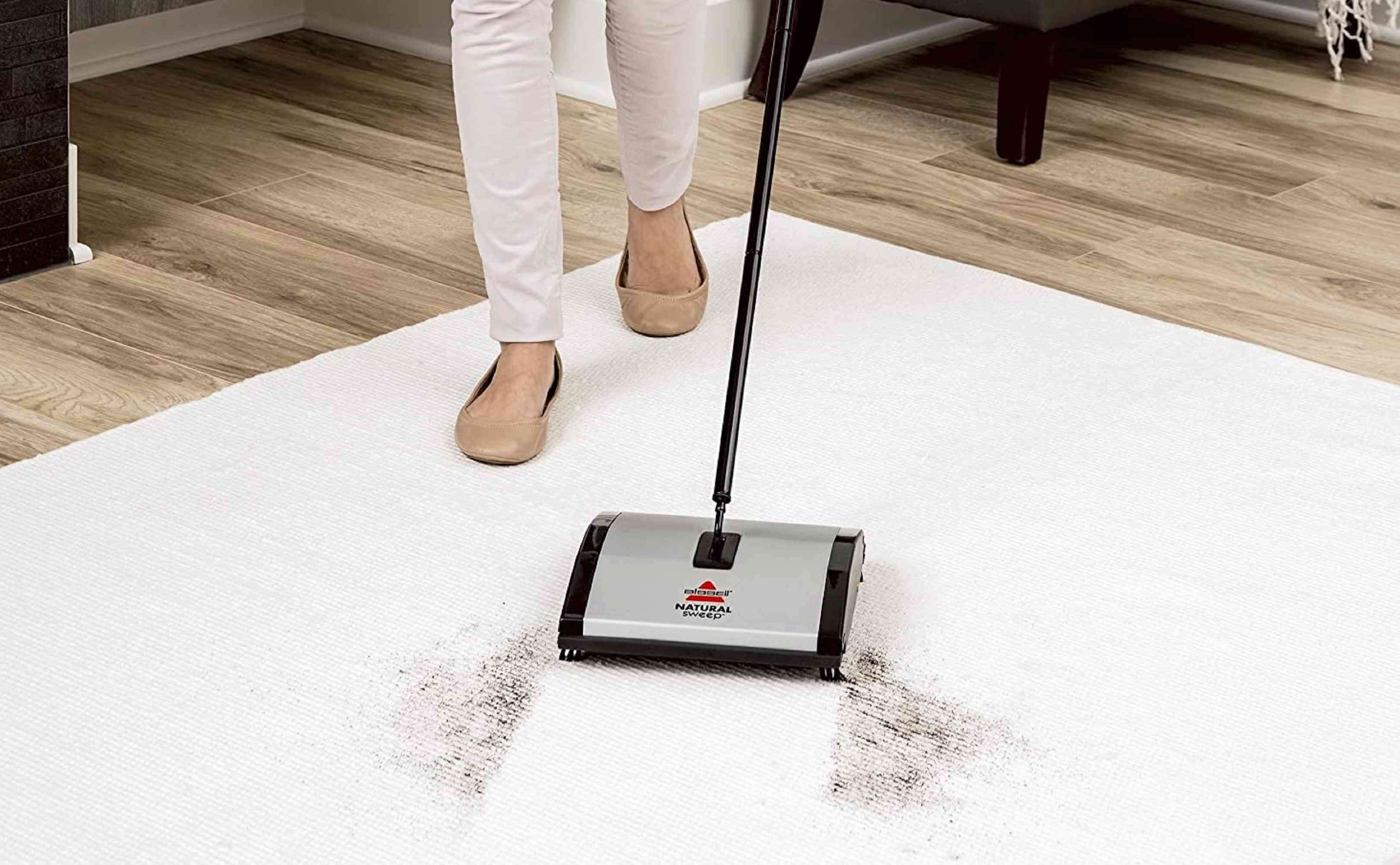 Woman using a Bissell Carpet Sweeper on a white carpet