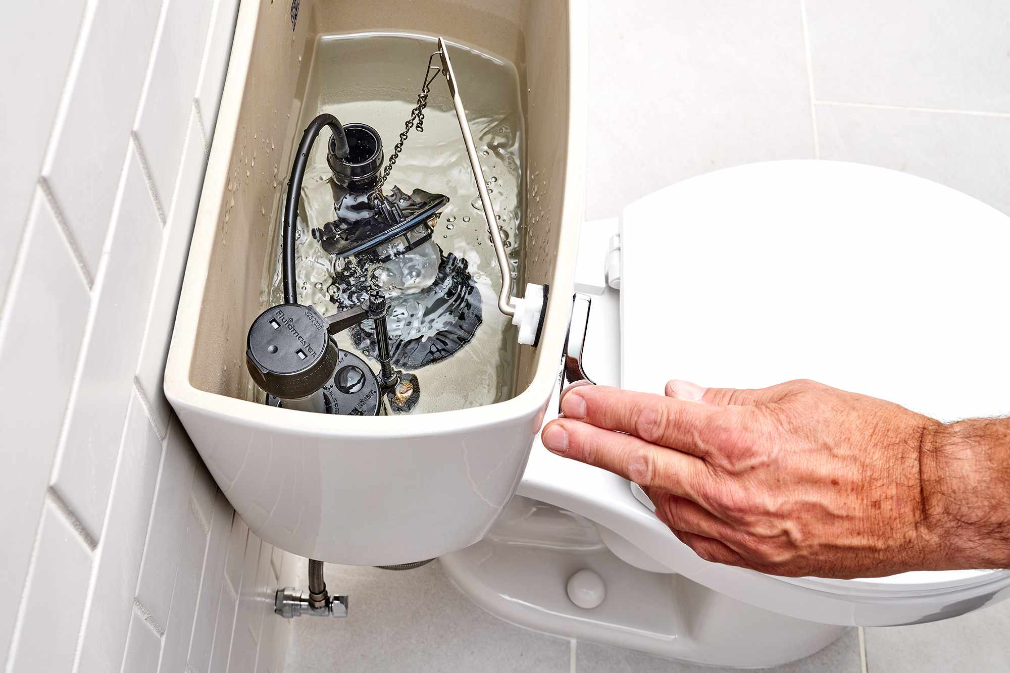 Toilet tank refilled with water with handle pushed down to check fill valve
