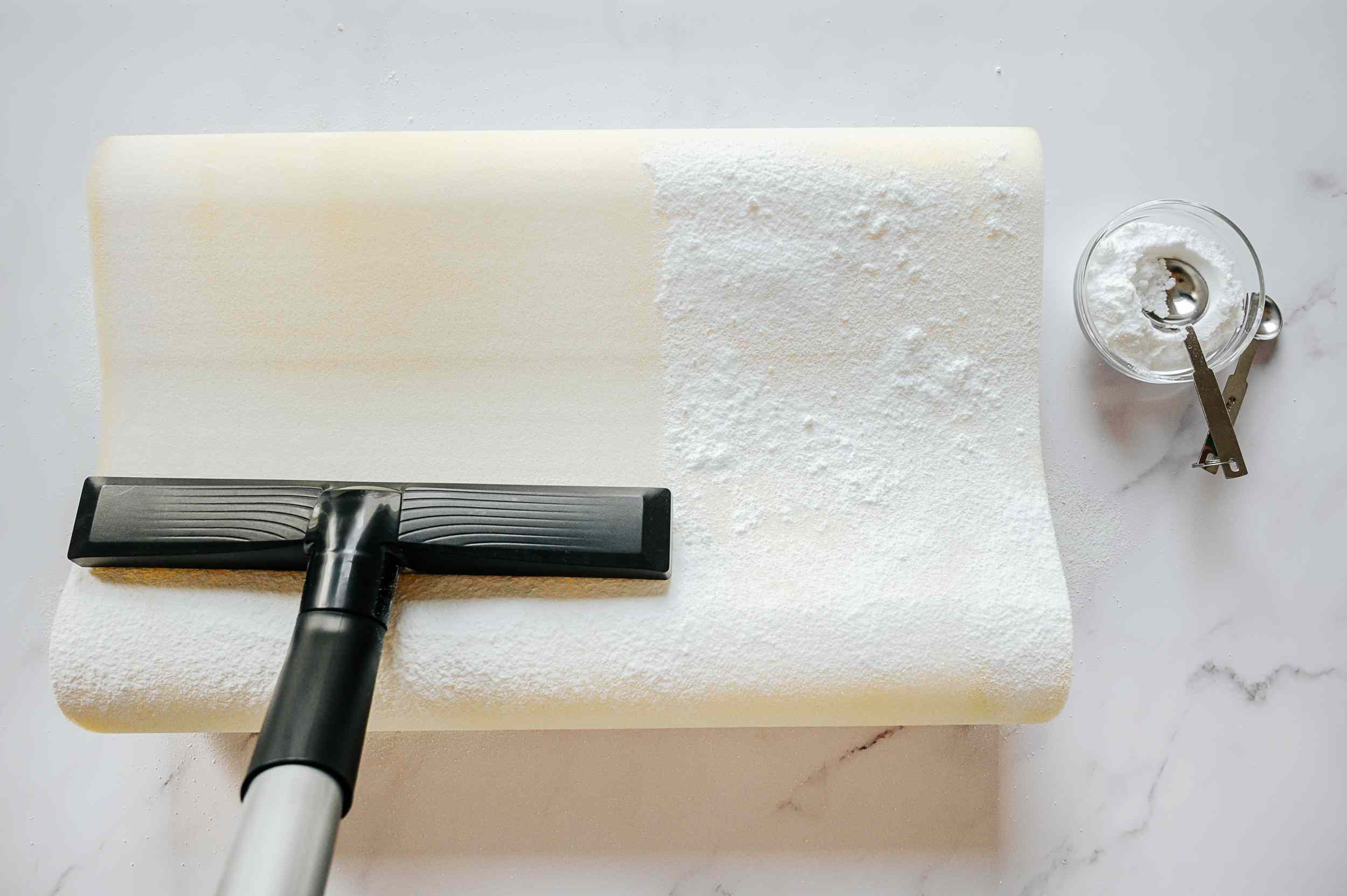 Memory foam bed pillow covered in baking soda and vacuumed for freshness