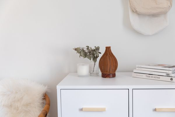 Brown woven oil diffuser on white dresser next to branch in vase, candle and stack of books