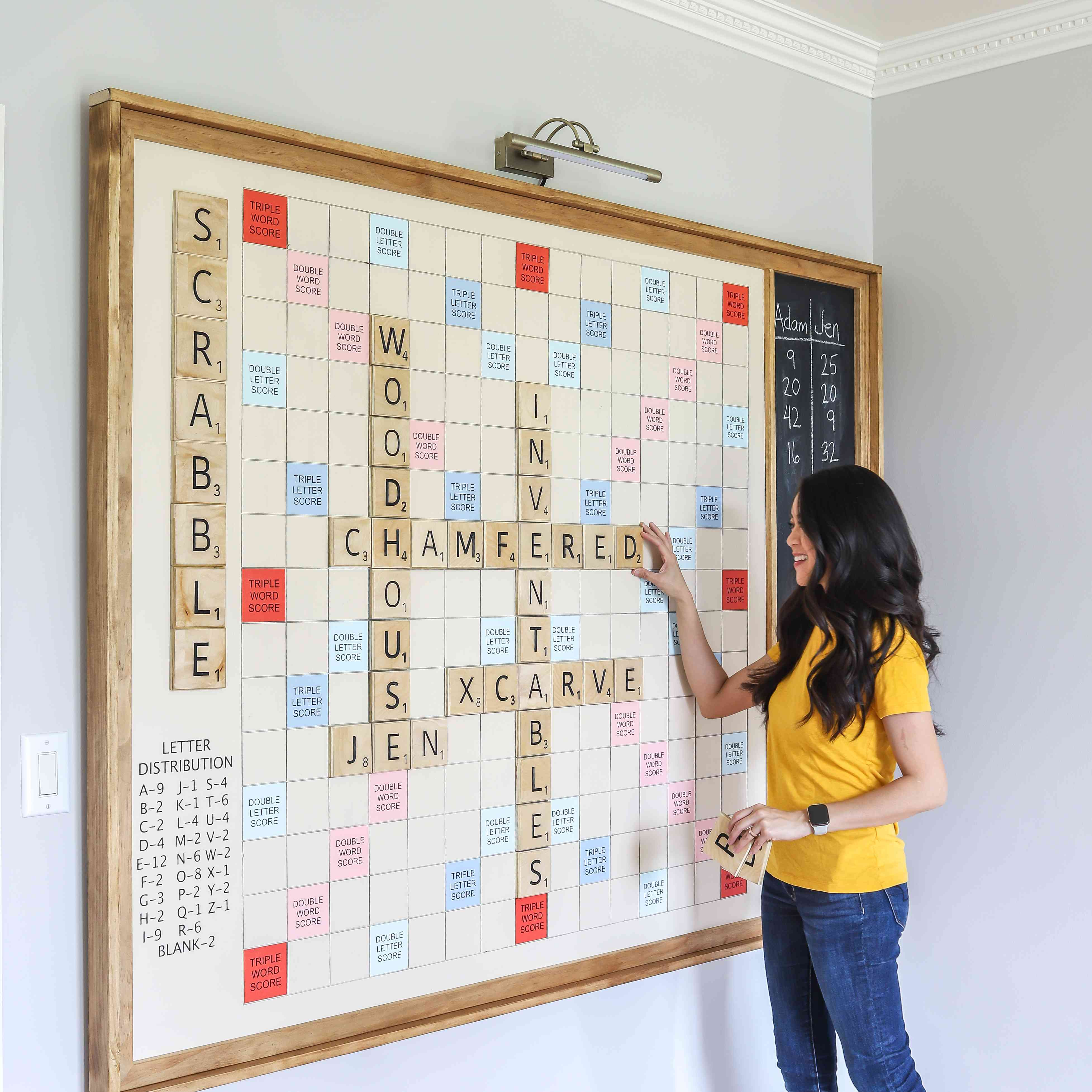 Jen Woodhouse poses next to her DIY giant Scrabble board mounted on a wall