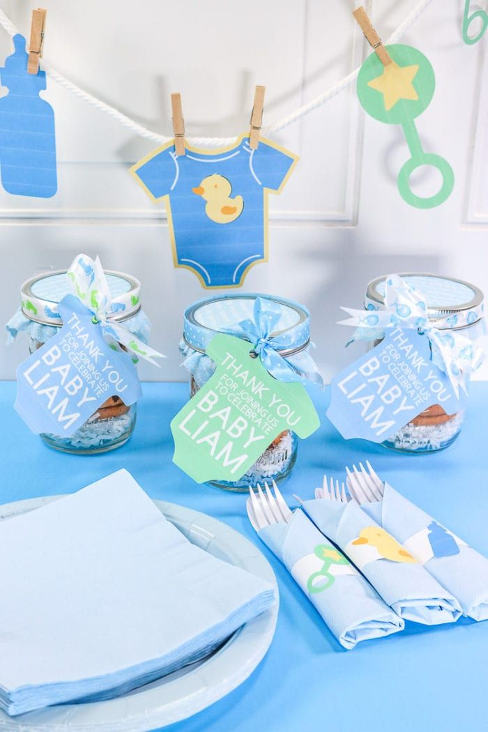 A baby shower table with favors and a banner