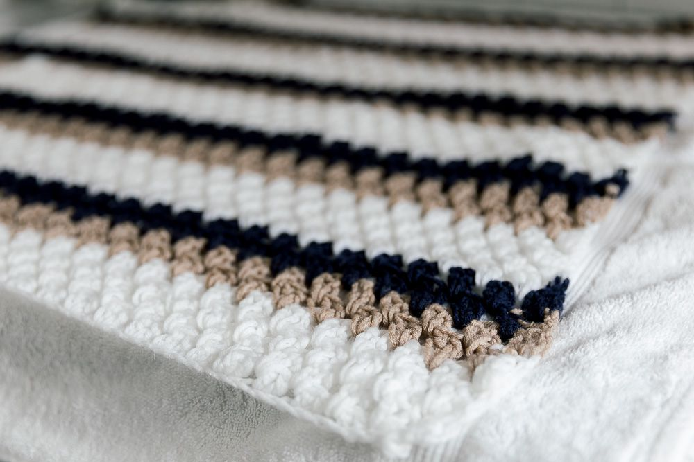 A crochet blanket laying flat to dry