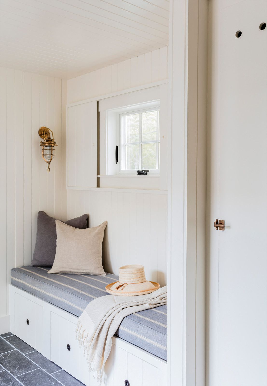 small mudroom bench below a window in a white cottage