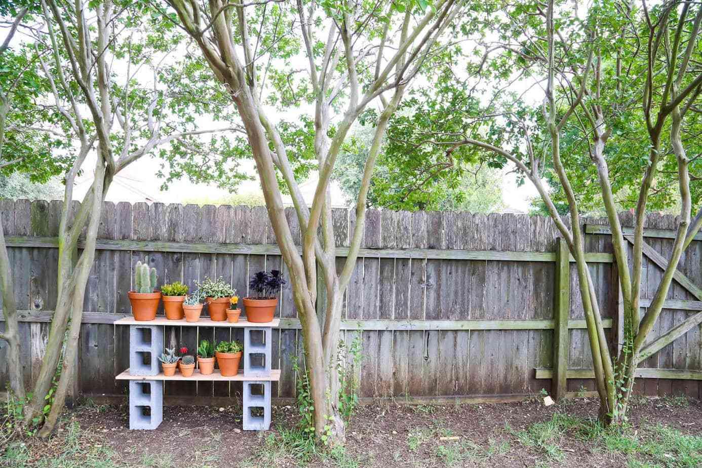 A cinder block plant shelf in a backyard
