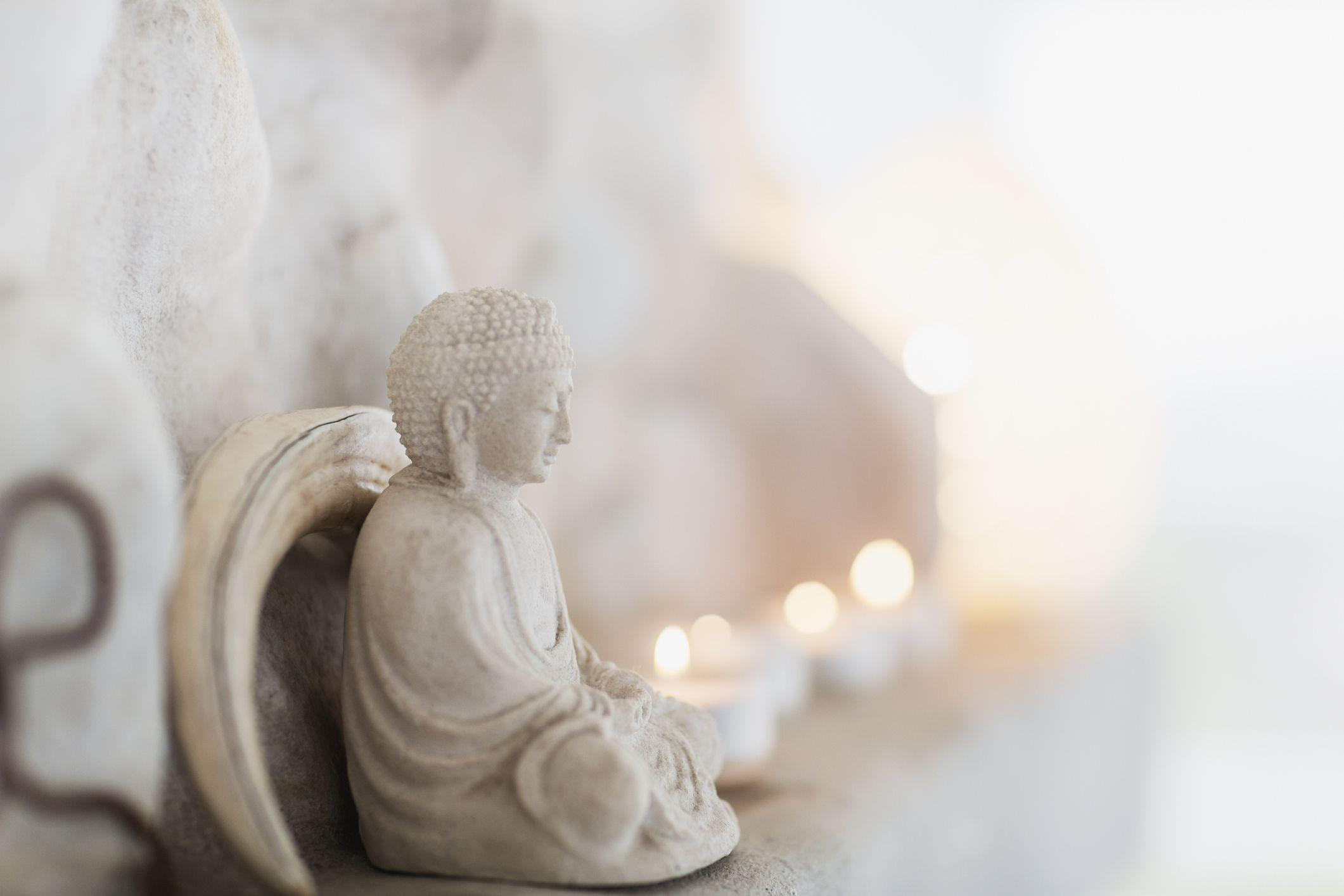 White Buddha statue with tea lights