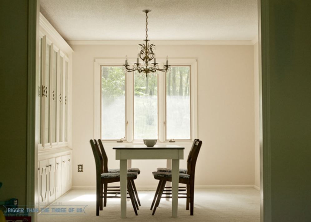 All white dining room with wall of built-ins.