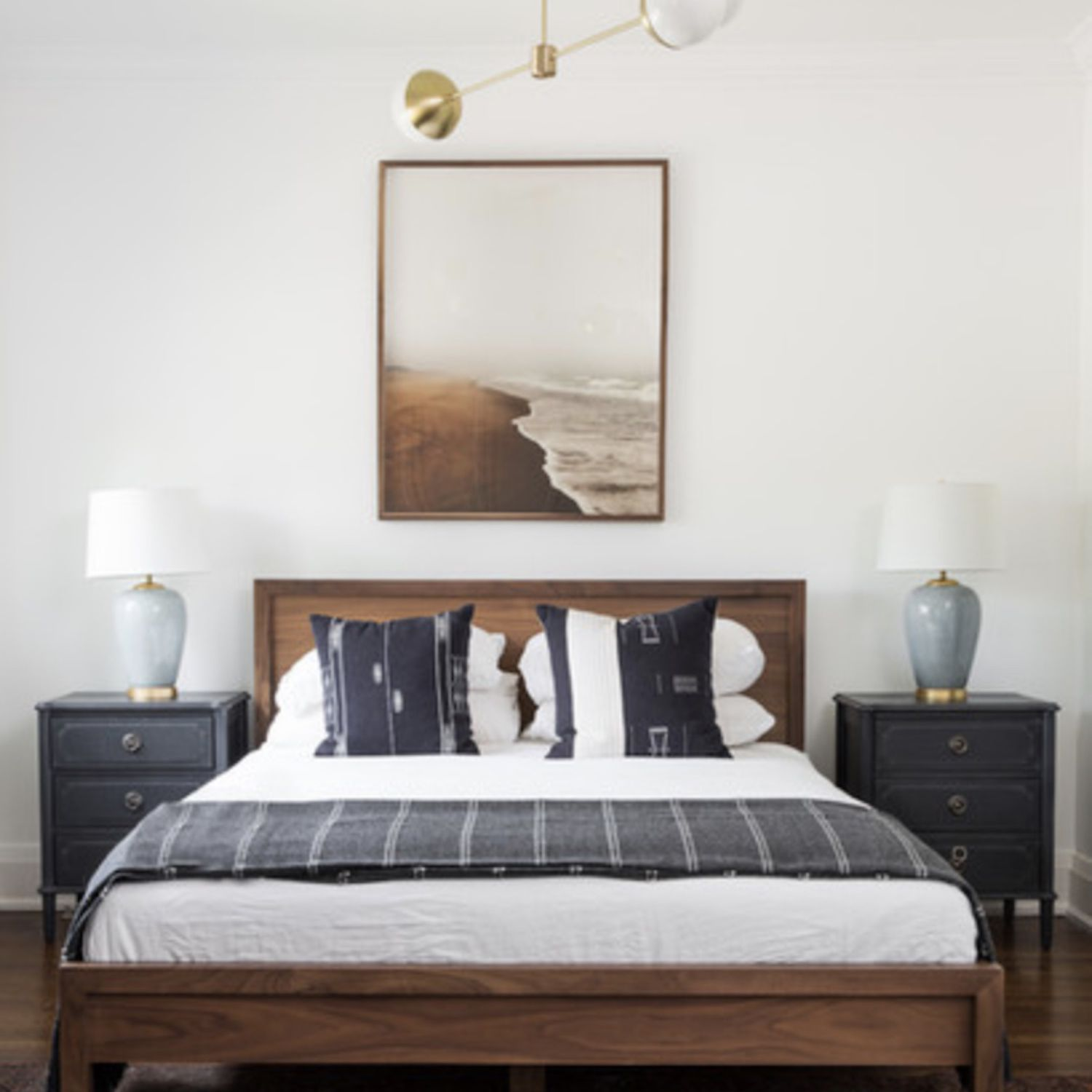 bedroom with wooden headboard, blue and white and brown color scheme, modern light fixture on ceiling