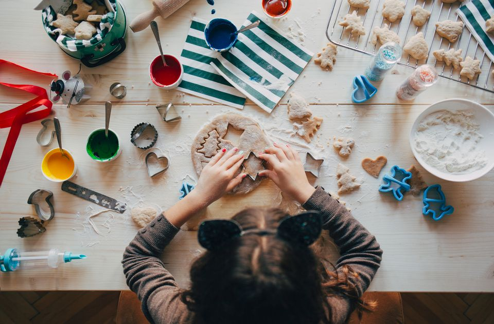 Young girl decorating and baking christmas cookies