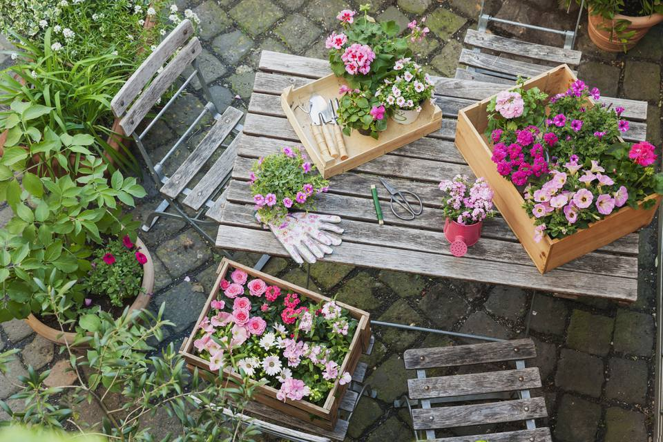 Three wooden crate container gardens on patio table
