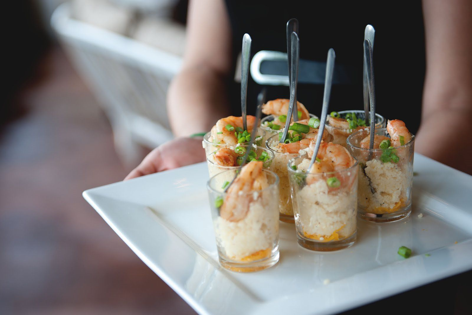 Mini shrimp and grits served on a square plate