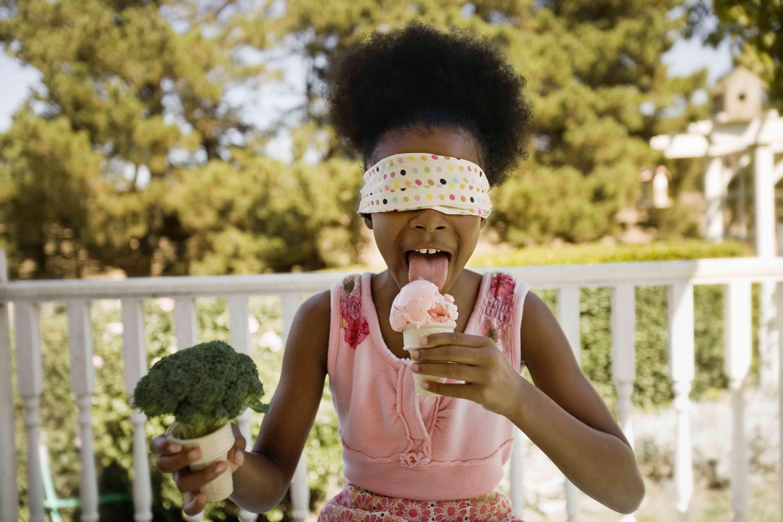 Blindfolded girl licks ice cream