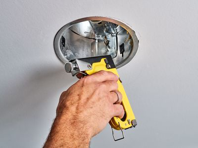 Recessed lights' spring clips being fixed with yellow staple gun