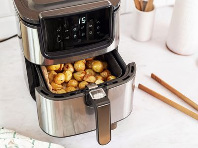 Stainless steel air fryer with cooked potatoes next to kitchenware