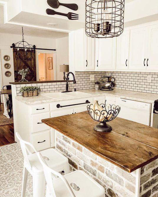 Cocina con vigas de madera e isla de cocina de madera y blanca