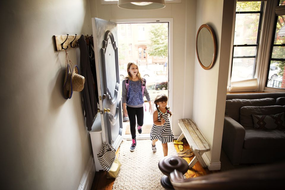 Sisters entering home entryway