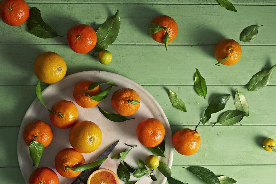 Oranges scattered across green table