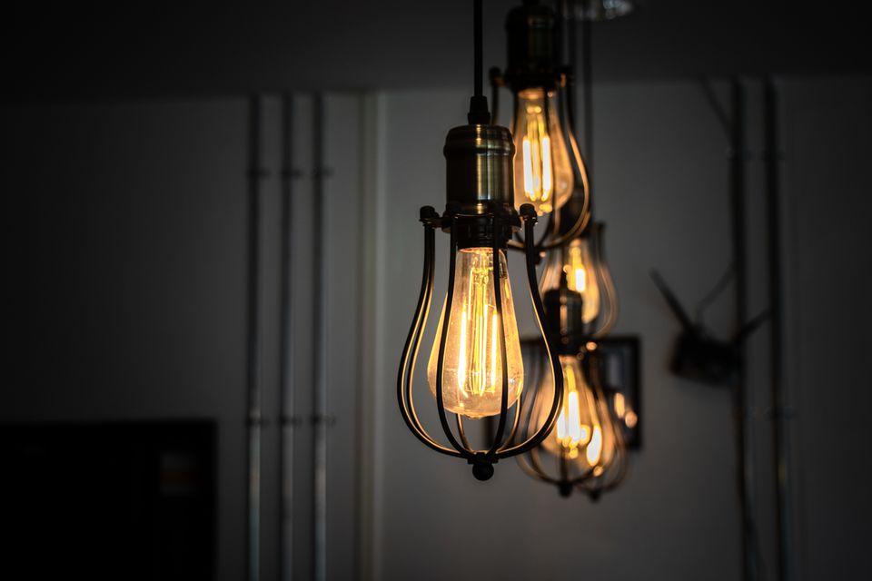 Luces colgantes iluminadas con bombillas incandescentes de ámbar colgando en casa
