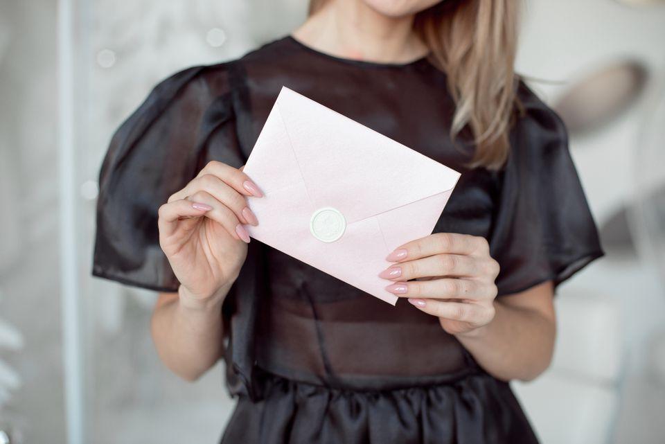 woman holding pink envelope