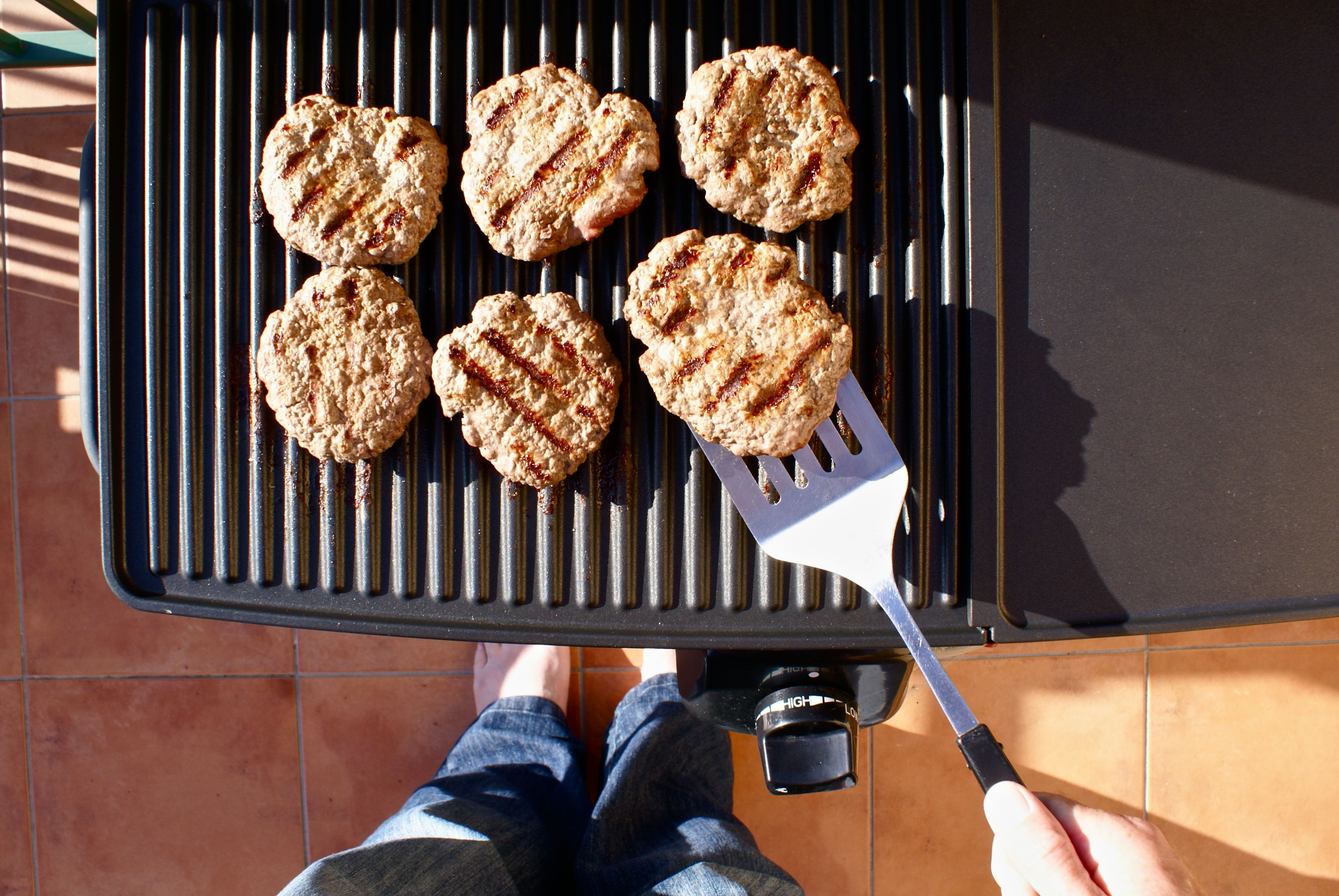 Person flipping burgers on a grill.