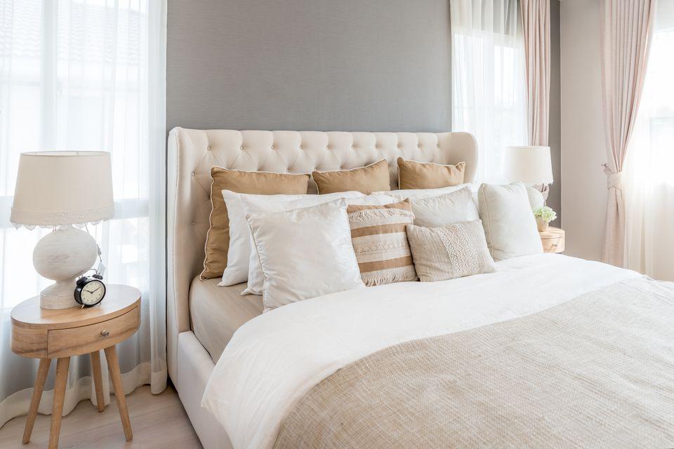 Dormitorio en colores claros y suaves. Cama doble grande y cómoda en un elegante dormitorio clásico en casa.