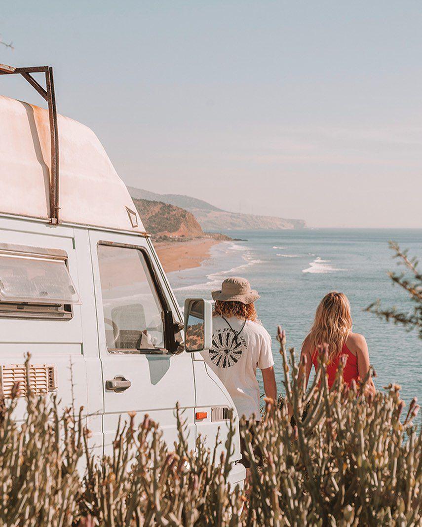 Una pareja mirando la costa con su camioneta detrás de ellos.
