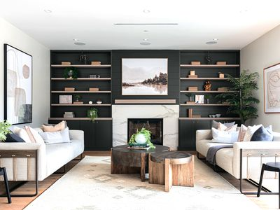 Living room with green accent wall and wood shelving on side of white fireplace
